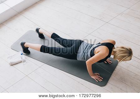 Young happy attractive woman doing push ups or press ups exercise. Slim sporty girl working hard on the mat. View from the above