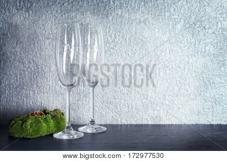 Moss with wedding rings and champagne glasses on table and grey wall background