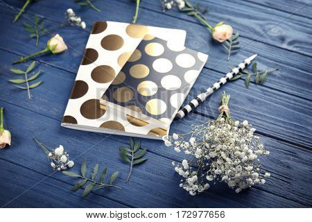 Composition of flowers and copybooks on blue wooden background
