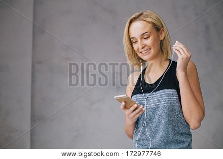 Beautiful young woman in sports wear and earphones is listening to music using a smartphone. Happy girl holding one earphone with left hand. Isolated. Close up