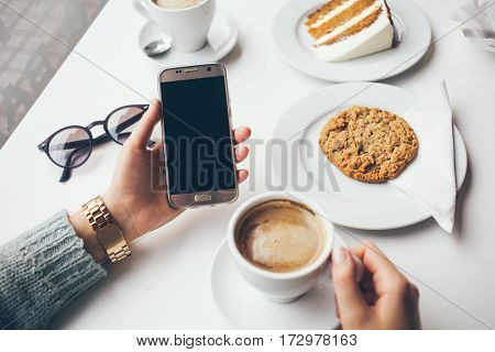 Close-up of woman's hand holding cell phone while drinking coffee and eating oat cookie. Reading news surfing the web / internetchatting in social network in smartphone. Blurred background.