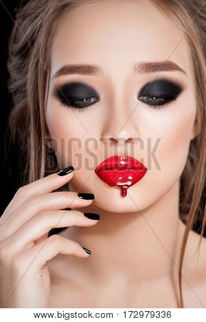 Gorgeous Young Woman face portrait. Beauty Model Girl with bright eyebrows, perfect make-up, red lips, touching her face. lady makeup for party. Isolated on black background. Smokey eyes. Studio