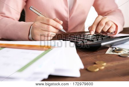 Woman sitting at table with calculator