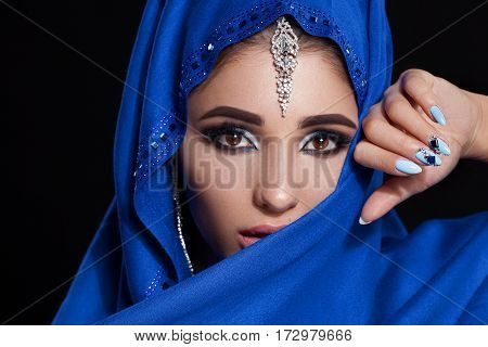 Gorgeous Young East Woman face portrait. Beauty Model Girl with bright eyebrows, perfect make-up, touching her face. Traditional. Isolated on black background. Smokey eyes