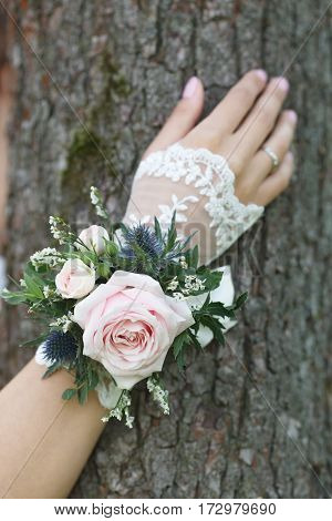 Pale pink, blue and green wrist corsage on a hand