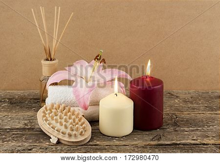 Beautiful composition with candles, spa towels and massage brush on wooden background, spa and body care concept