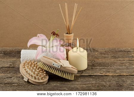 Beautiful composition with white candle and massage brushes on wooden background, weight loss and skin care concept