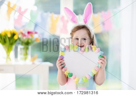 Happy little girl in bunny ears holding a heart board with colorful Easter eggs. Kids celebrate Easter. Children having fun on Easter egg hunt. Pastel bunny banner and flowers. Space for your text.