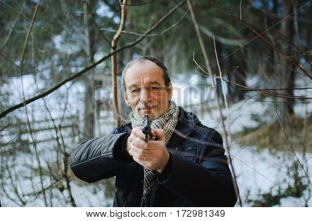 An elderly man with a gun in the woods in early spring. Man dressed in a black jacket and scarf. He holds the gun in both hands and aiming straight forward