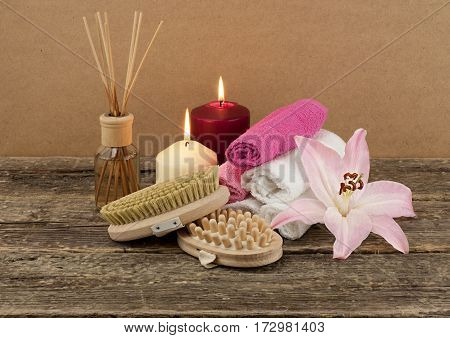 Beautiful composition with two candles, aromatic oil and massage brushes on wooden background, skin and body concept