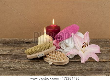 Beautiful composition with two candles and massage brushes on wooden background, skin and body care concept