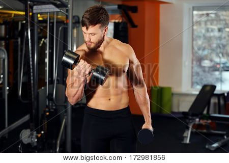 Young handsome man with dumbbells training in gym