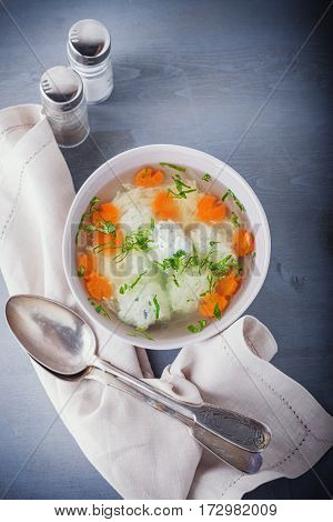 Chicken soup with meatballs and vegetables on a table