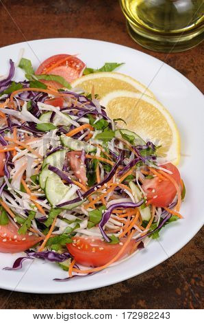 Salad of white and blue chopped cabbage carrots cucumber tomato dressed with oil lemon sesame