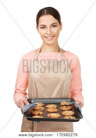 Young woman in apron holding baking tray with cookies on white background