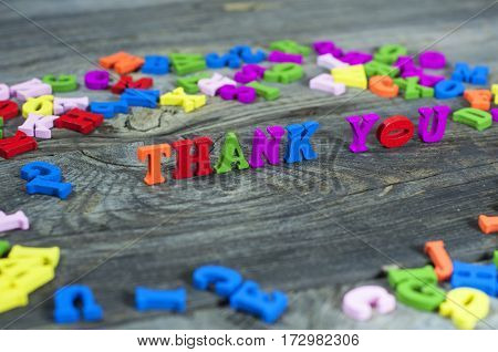 Colorful wooden letters on a gray surface the words thank you