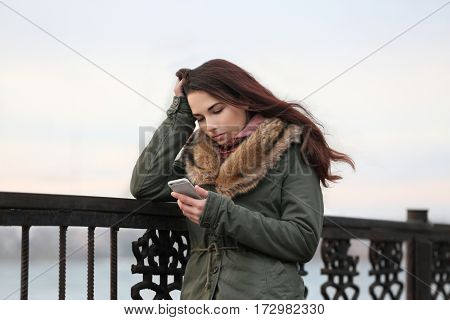 Depressed young woman with phone on pier