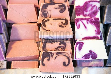 Pile of natural handmade soaps for sale. Stack of different handmade soaps on retail market