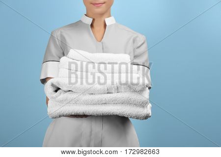 Female chambermaid holding clean white folded towels on color background