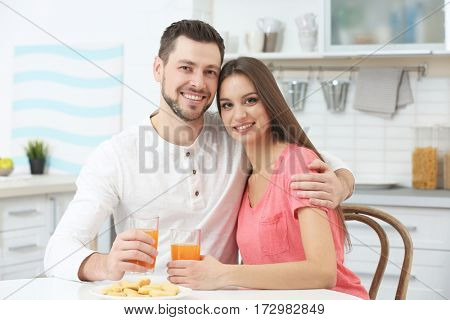 Beautiful young couple with orange juice sitting at kitchen table