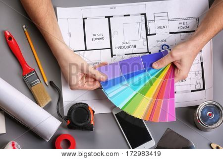 Decorator's hands holding color swatches. Project drawing and paint tools on work table