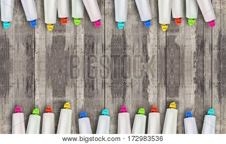 Tubes of paint on a wooden background