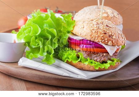 Cheeseburger with salad, onion tomato and fresh bread