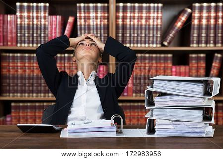 Close-up Of A Young Stressed Female Accountant Working With Stacked Folders