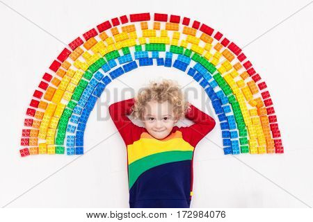 Child Playing With Rainbow Plastic Blocks Toy