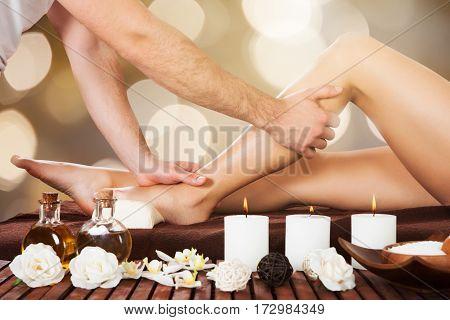 Close-up Of A Therapist Massaging Female Customer's Leg At Beauty Spa