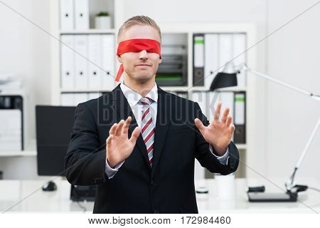 Portrait Of A Blindfolded Young Businessman Gesturing In Office