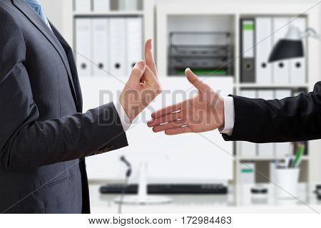 Close-up Of A Businessman Showing Middle Finger To Partner Offering Handshake In Office
