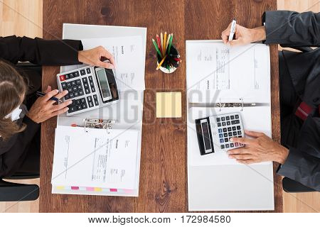 Two Accountants Calculating Tax Invoice Using Calculator On Wooden Desk