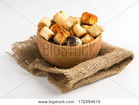 Salty party snack in wooden bowl on natural jute. White background.