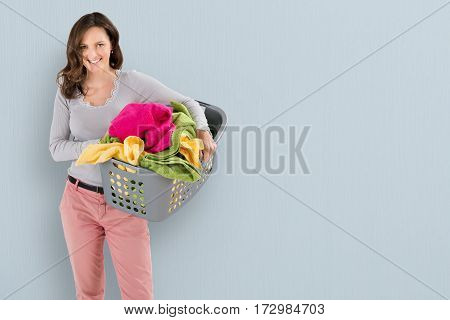 Portrait Of A Happy Woman Carrying Laundry Basket On Colored Background