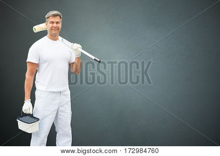 Portrait Of A Young Male Painter In White Uniform Standing With Paint Roller