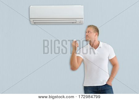 Young Man Holding Remote Control In Front Of Air Conditioner At Home