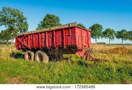 Old striking red colored agriculture trailer parked in the field on a sunny day in the summer season.