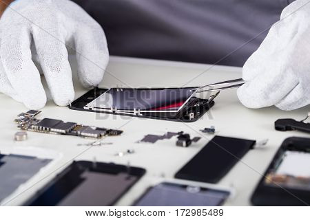 Close-up Of Repairman Disassembling Smartphone With Tweezers