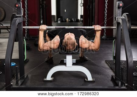 Young Man Lying On Bench Press While Exercising With Barbell In The Gym