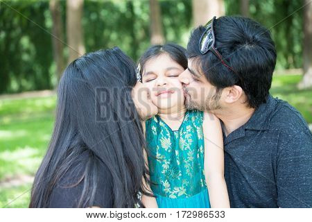 Closeup portrait young girl being kissed my parents and not liking it isolated outdoors outside background