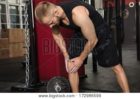 Man Suffering From Knee Pain After Exercise In The Gym
