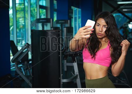 Woman take selfie in fitness club background after exercising. Pretty sporty woman take self photo in gym