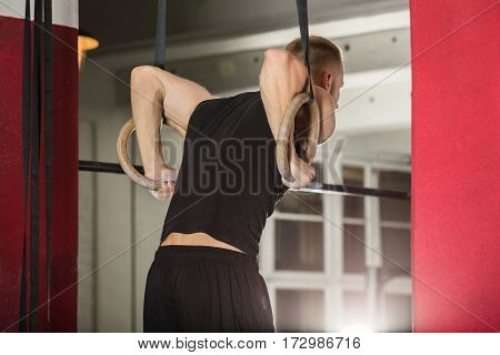 Young Fit Man Pulling Up On Gymnastic Rings In The Gym