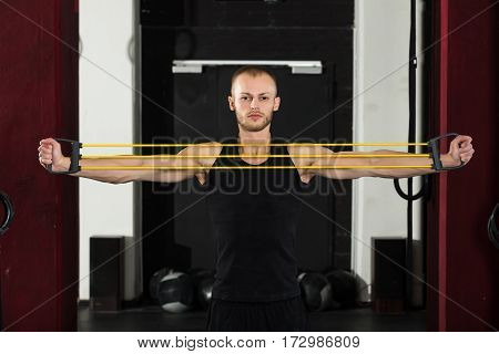 Portrait Of An Athlete Man Working With Stretch Band In The Gym