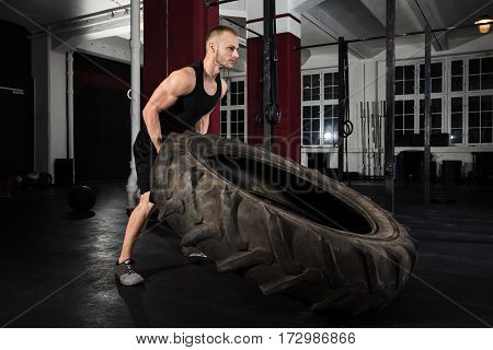 Young Athlete Man Pushing Truck Tire In The Gym