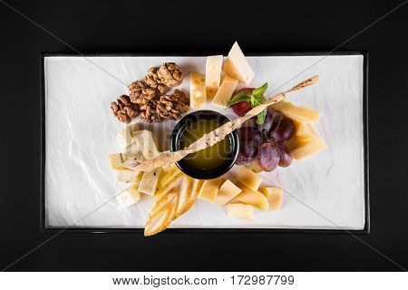 A large plate with a wide selection of snacks like grapes, cheese, walnuts, crackers on dark background. top view.