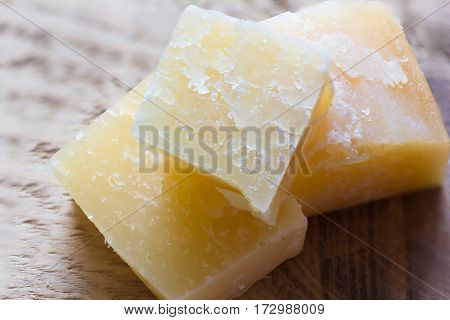 pieces of parmesan cheese on a wooden background