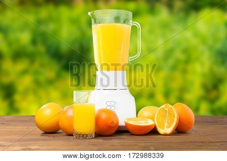 Fresh orange fruit and glass of orange juice or smoothies refreshment drinking on wooden rustic table in green garden background with blender. Healthy food. Tasty drink. Ecological environment