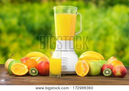 Fresh exotic fruit and glass of multifruit juice or smoothies refreshment drinking on wooden rustic table in green garden background with blender. Healthy food. Tasty drink. Ecological environment